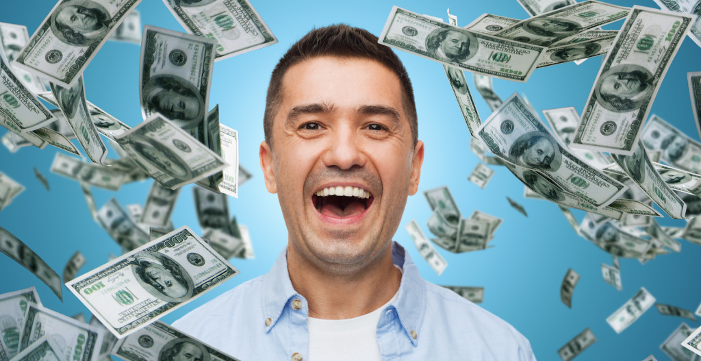 business, finance, success, emotions and people concept - laughing man over blue background with heap of falling dollar money